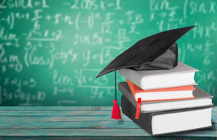 Mortarboard bovenop boekenstapel met rekensommen op achtergrond